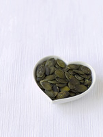 Pumpkin seeds in a heart-shaped bowl