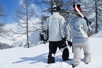 Rear view of couple walking away from camera, holding winter sport equipments