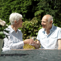 Senior couple resting in the garden, drinking wine