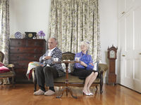 Senior couple sitting at opposite ends of sofa with arms crossed