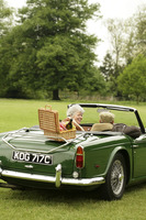 Senior couple sitting in the car with a picnic basket on the back