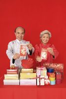 Senior man and senior woman holding red packets and smiling