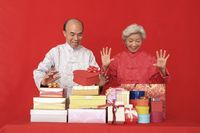 Senior man and senior woman looking excited at gift boxes and paper bags