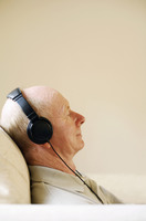 Senior man closing his eyes while listening to music on the headphones