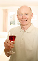 Senior man holding a glass of red wine