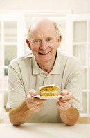 Senior man holding a plate of cake