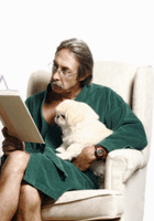 Senior man hugging his dog while reading book on the couch