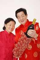 Senior man is showing senior woman a bottle of wine