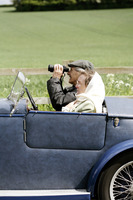 Senior man using binoculars while sitting in the car