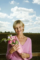 Senior woman holding a bouquet of flowers while smiling at the camera