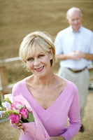 Senior woman holding a bouquet of flowers with her husband standing in the background