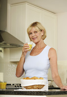 Senior woman holding a glass of orange juice while smiling at the camera