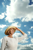 Senior woman holding her hat while looking up