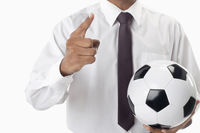 Soccer manager holding a ball and pointing