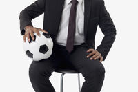 Soccer manager holding a ball on his lap