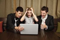 Stressed business people looking at laptop