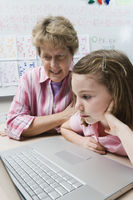 Teacher helping schoolgirl use laptop
