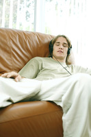 Teenage boy closing his eyes while listening to music on the headphones