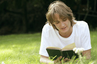 Teenage boy lying forward on the field reading book