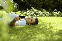 Teenage boy lying on the field taking his own picture with camera phone