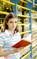 Teenage girl looking at the camera while holding a book