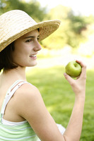 Teenage girl sitting on the field holding a green apple