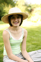 Teenage girl with hat sitting on the field