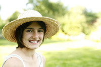 Teenage girl with hat smiling at the camera