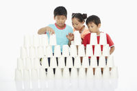 Three children stacking up disposable cups