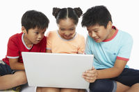 Three children using a laptop together