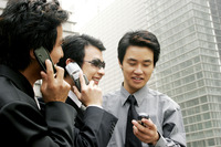 Three men in office attires using hand phones