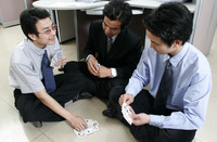 Three men playing cards in the office