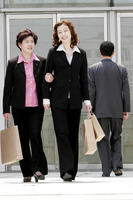 Two business women carrying paper bags