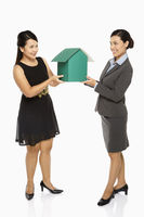 Two businesswoman holding up a cardboard house