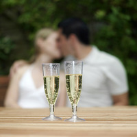 Two glasses of champagne with couple kissing in the background