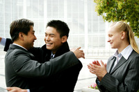 Two men hugging each other while a woman clapping her hands