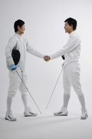 Two men in fencing suits shaking hands
