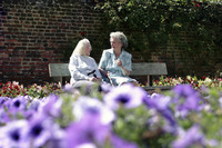 Two old women sitting on a bench in the garden talking