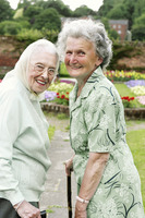 Two old women with walking sticks walking in the park