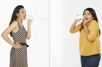 Two women communicating through a paper cup phone