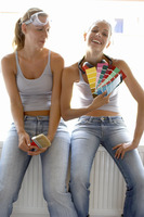 Two women in jeans sitting together with one holding a brush while the other holding colour cards