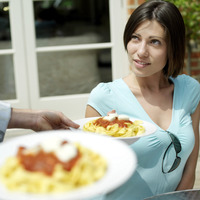 Waiter serving woman spaghetti