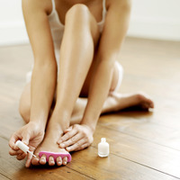 Woman applying nail polish on her toe nails
