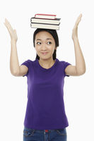 Woman balancing a stack of books on her head