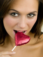 Woman biting a heart-shaped chocolate