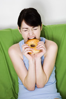 Woman biting on a doughnut