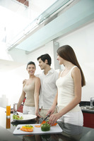 Woman cutting vegetables in the kitchen with her friends beside her