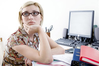Woman daydreaming at desk in a home office