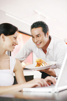 Woman getting a delicious dish from her boyfriend while using laptop