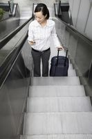 Woman going up escalator with suitcase, text messaging at the same time